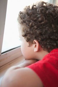 boy in red shirt looking out window